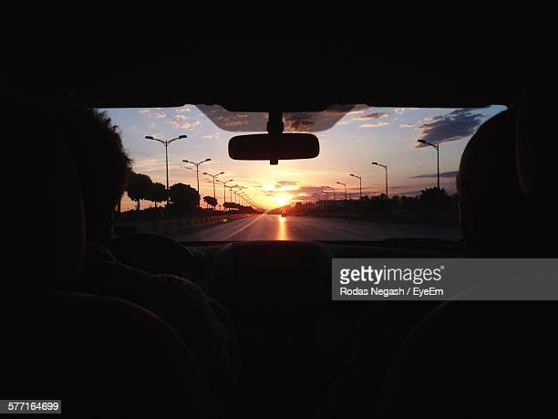 Silhouette People In Car Against Orange Sky