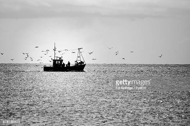 Silhouette People In Trawler On Sea Against Sky