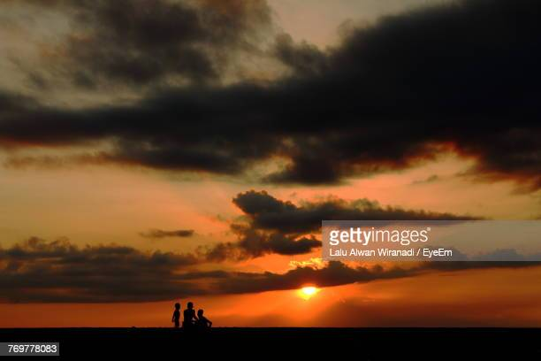 Silhouette People On Field Against Dramatic Sky During Sunset