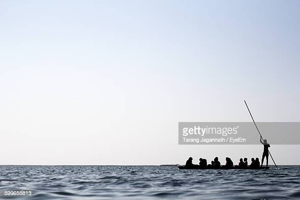 Silhouette People On Wooden Raft Sailing In Sea