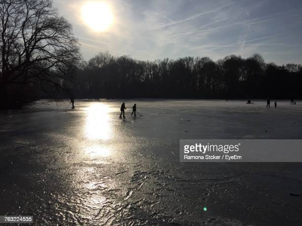 Silhouette People Playing Ice Hockey Against Sky