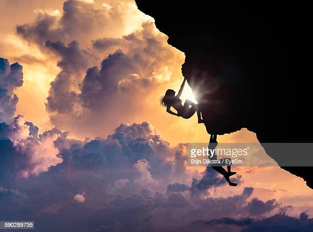 Silhouette People Rock Climbing Against Sunset Sky