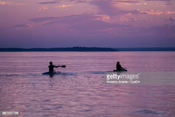 Silhouette People Rowing Boats On Sea Against Sky During Sunset