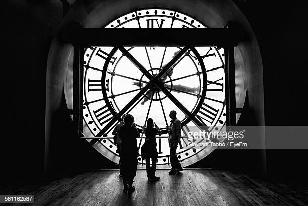 Silhouette People Standing Against Large Clock