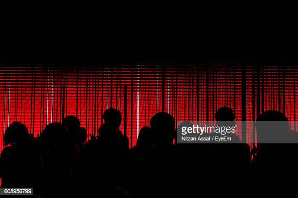 Silhouette People Standing Against Red Illuminated Wall
