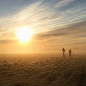 Silhouette People Standing On Field Against Sky At Foggy Weather During Morning