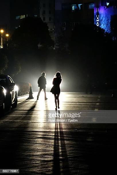 Silhouette People Walking On Illuminated Street At Night