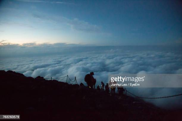 Silhouette People Walking On Mountain Against Cloudscape During Sunset