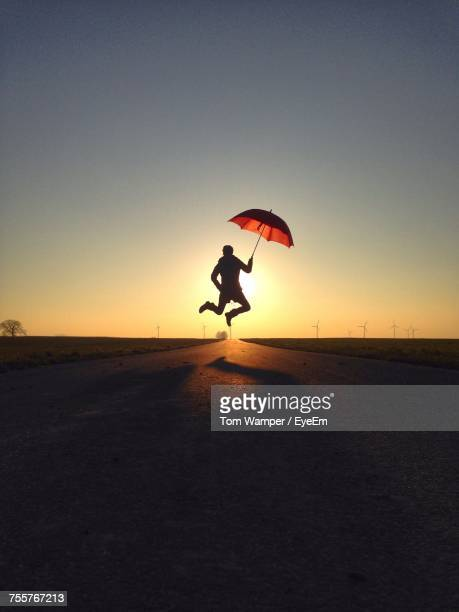 Silhouette Person Jumping On Road Against Clear Sky