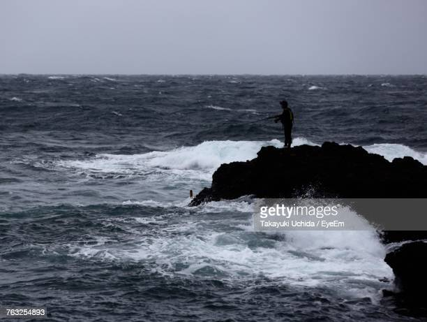 Silhouette Person Standing At Sea Against Clear Sky