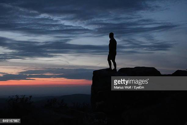 Silhouette Person Standing On Cliff Against Cloudy Sky