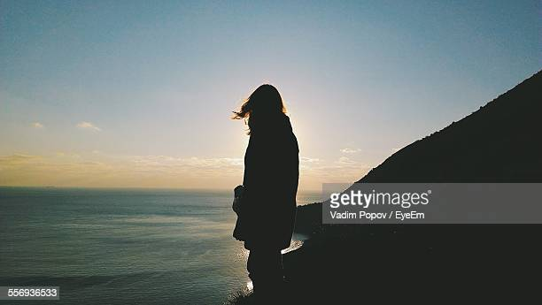 Silhouette Person Standing On Cliff By Sea Against Sky
