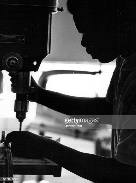 Silhouette photograph shows Ernest Wells 1443 Mariposa St ninth grader operates drill press drilling axle holes in wooden pulley wheel Credit Denver...