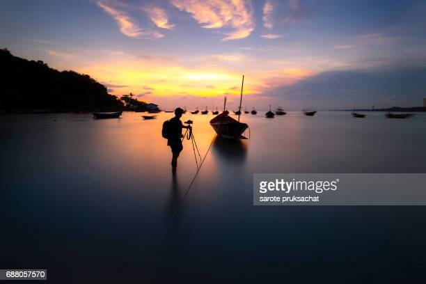 silhouette photographer Shooting fishing boat and sunset .