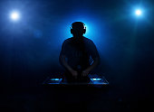 Silhouette of a disc jockey mixing in the night club with copy space