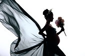 Silhouette Portrait of Pregnant woman hold bouquet flower and fabric fluttering in Air waving fashion style, Studio lighting white background, low exposure