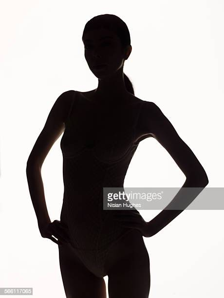silhouette portrait of woman, hands on hips