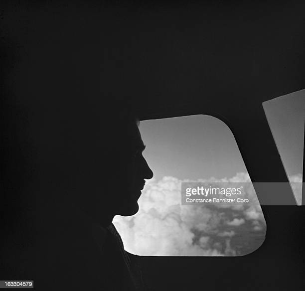 A silhouette profile of a pilot flying a plane in the clouds