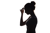 silhouette of a young graceful woman with hand near forehead, profile of a beautiful girl on a white isolated background, concept beauty and fashion