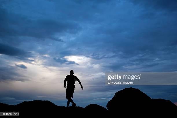 silhouette running man dramatic sky