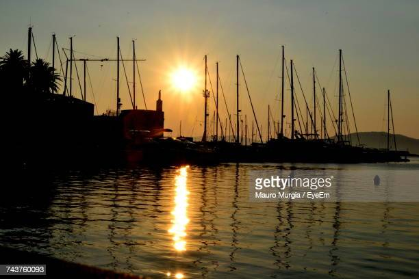 Silhouette Sailboats In Harbor Against Sky During Sunset