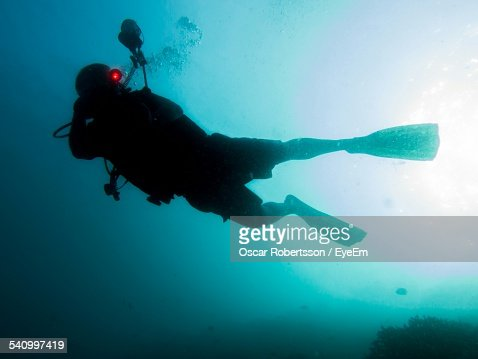 Silhouette Scuba Diver Swimming Through Blue Ocean