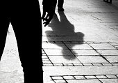 Shadow silhouette of two person on city sidewalk in black and white