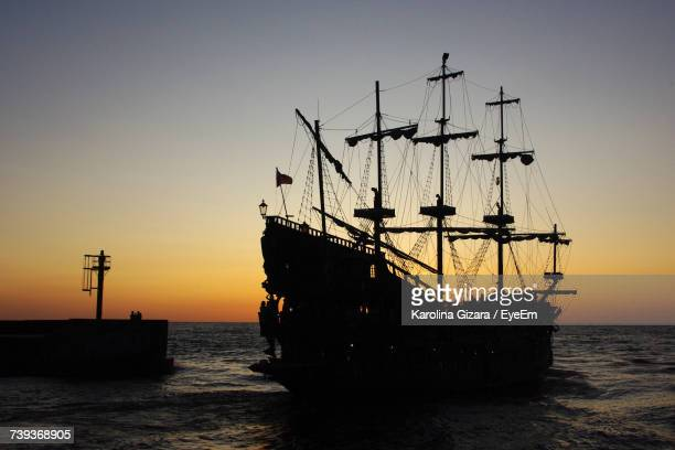 Silhouette Ship Moored At Harbor Against Clear Sky
