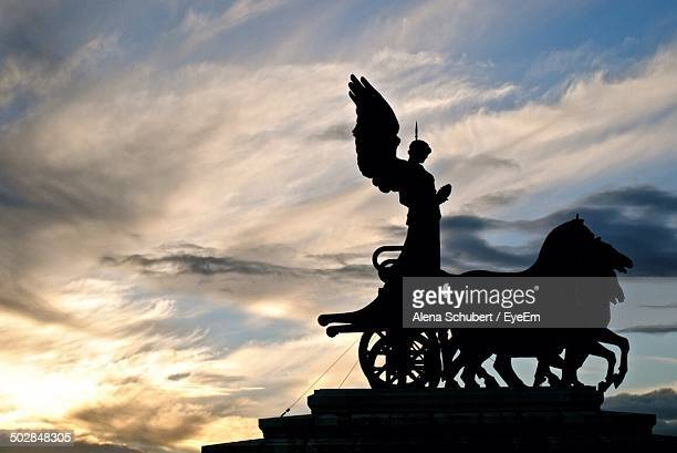 Silhouette statue of goddess Victoria riding quadriga against cloudy sky