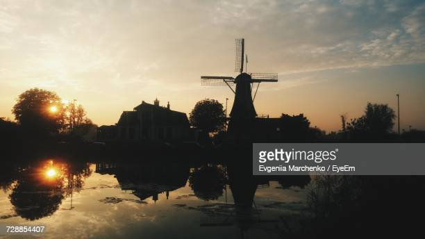 Silhouette Traditional Windmill By Lake Against Sky During Sunset
