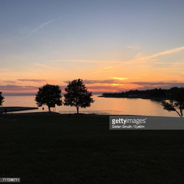Silhouette Trees On Calm Countryside Lake At Sunset