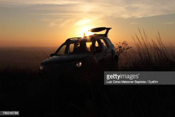 Silhouette Vehicle On Field Against Sky During Sunset