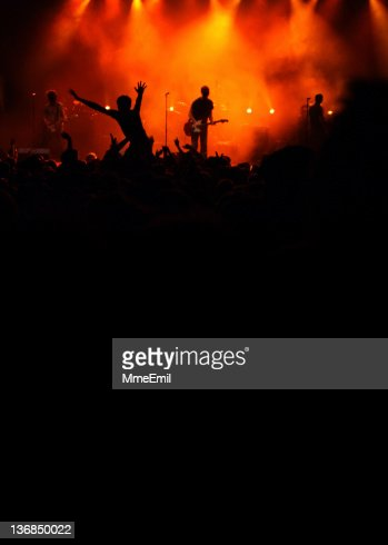 Silhouette view of a band and concert goers at rock concert
