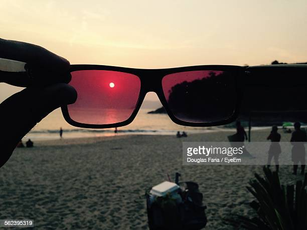 Silhouette View Of Sunset And People Holidaying On Beach Seen Through Sun Glasses
