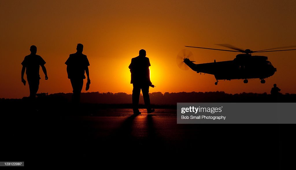 Silhouette view of three man and helicopter