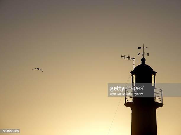 Silhouette Weather Vane On Top Of Tower Against Clear Sky At Dusk