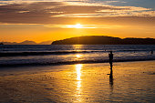 Silhouette woman standing on shore at beach during sunset at Aonang Krabi Thailand