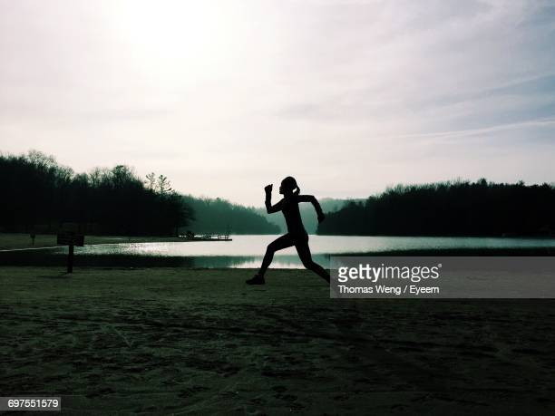 Silhouette Woman Jogging On Grassy Field By Lake Against Sky