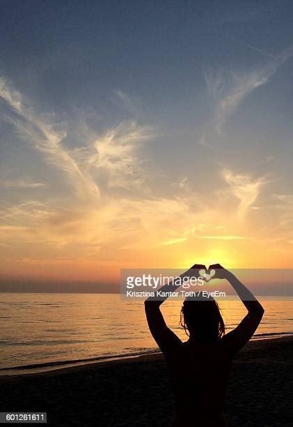 Silhouette Woman Making Heart Shape From Hands