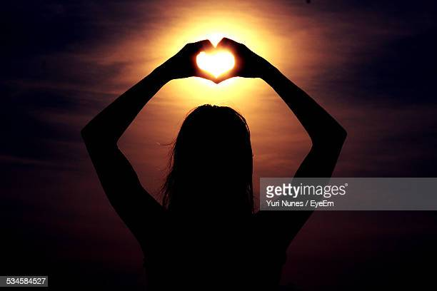 Silhouette Woman Making Heart Shape Sky During Sunset
