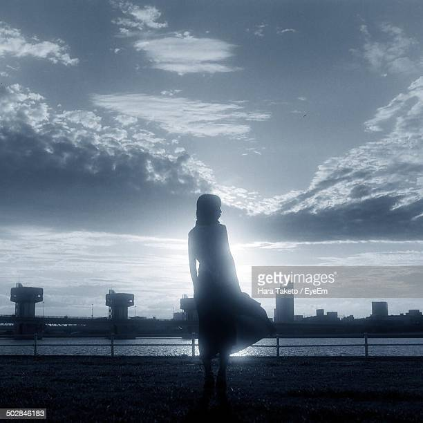 Silhouette woman on street with cityscape in background