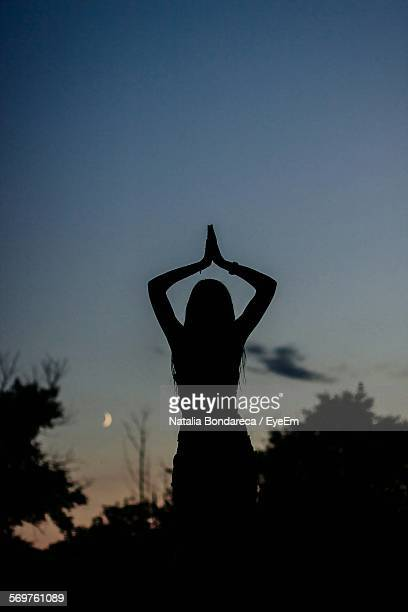 Silhouette Woman Performing Yoga On Field Against Sky At Sunset