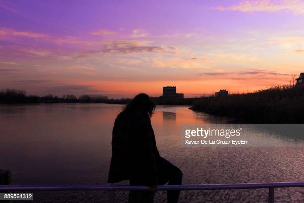 Silhouette Woman Sitting On Railing At Riverbank
