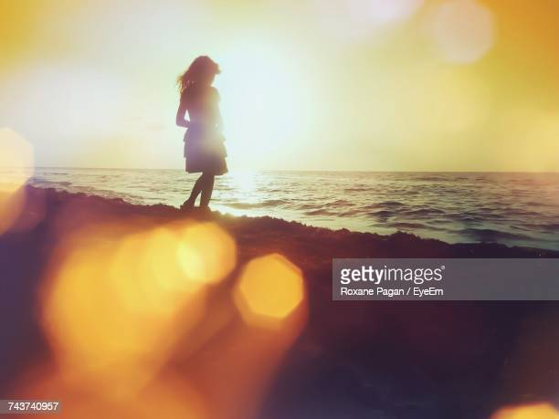Silhouette Woman Standing At Beach During Sunset