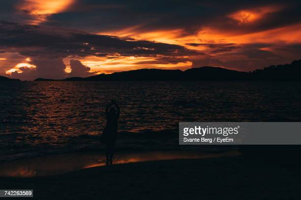 Silhouette Woman Standing By Shore Against Dramatic Sky During Sunset