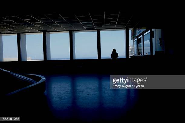 Silhouette Woman Standing By Windows In Airport