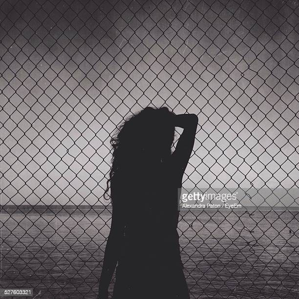Silhouette Woman Standing In Front Of Chainlink Fence