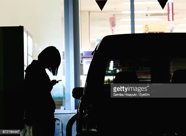 Silhouette Woman Using Mobile Phone By Car At Parking Lot