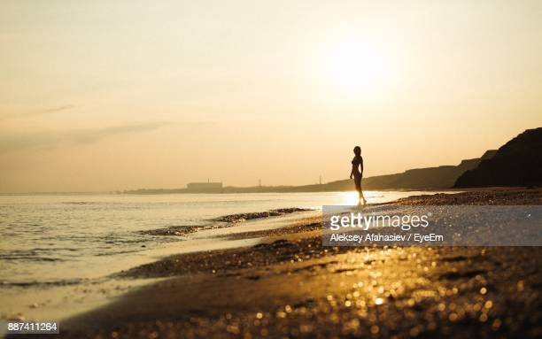 Silhouette Woman Walking At Beach Against Sky During Sunset