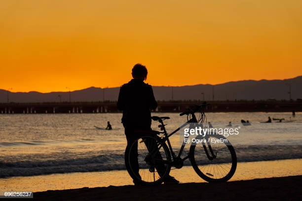 Silhouette Woman With Bicycle On Beach Against Sky During Sunset
